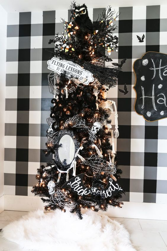 a black Halloween tree decorated with lights, candy corns, mirrors, skulls, a sign and skeletons