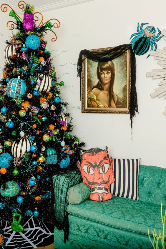 a black Halloween tree decorated with oversized striped black, white and blue ornaments, feathers and beads
