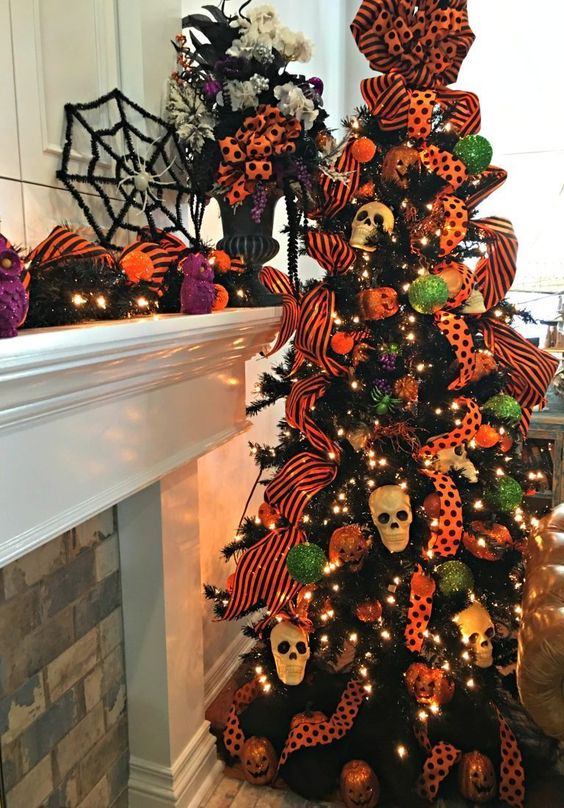a black Halloween tree with lights, bright orange ribbons, mini skulls and green and orange ornaments