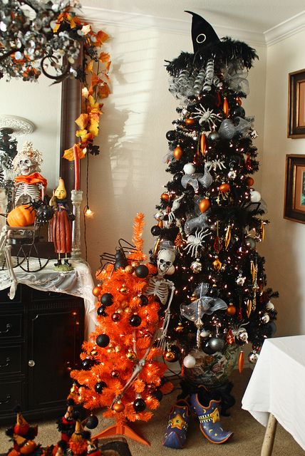 a black Halloween tree with lights, spiders, orange and black ornaments, a witch hat on top and some garlands and banners