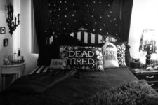 a black and white bedroom with printed pillows, a candelabra on the wall, a lamp and a dark canopy over the bed