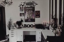 a black and white bedroom with scary busts, skulls, striped pumpkins, a watercolro rug and a Beetlejuice gallery wall
