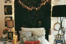 a black tapestry, lights, black lamps, moon phase artworks and a fun pillow add Halloween flavor to the bedroom