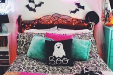 a bright Halloween bedroom done in pink, green, black and white, with bats, neon lights and lots of prints is super fun