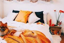 a bright Halloween bedroom with orange and black touches – bedding, letters, pumpkins and lanterns and even blooms