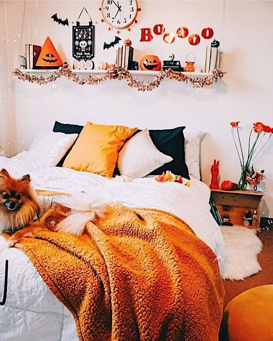a bright Halloween bedroom with orange and black touches - bedding, letters, pumpkins and lanterns and even blooms