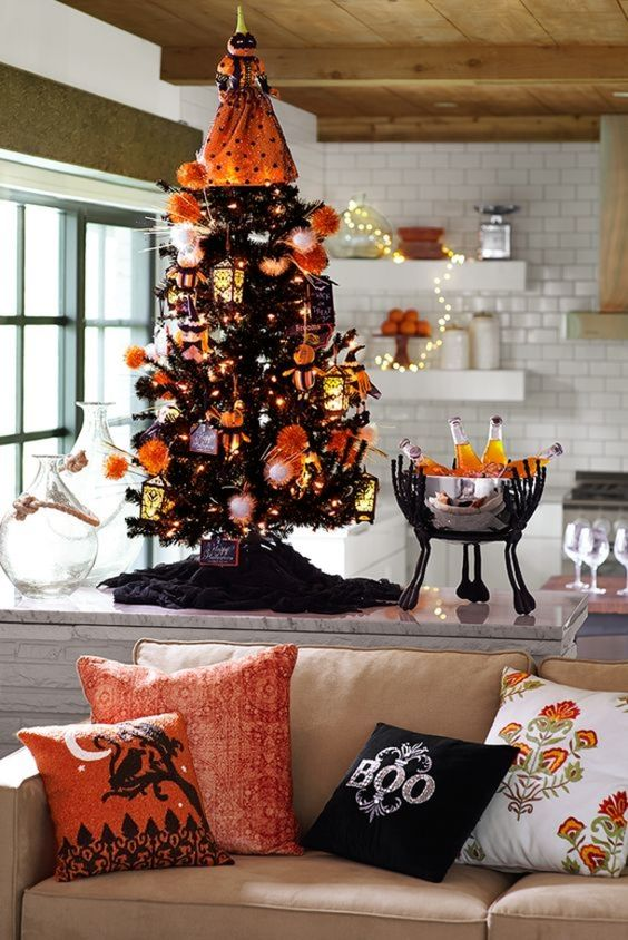 a mini black Halloween tree decorated with white and orange ornaments, lights and a scary pumpkin head doll on top