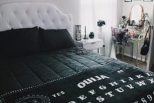 a monochromatic Halloween bedroom with a bat artwork, black bedding, a spiderweb candleholder, a scary photo on the wall