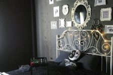 a moody Halloween bedroom in black, with a scary gallery wlal, a mirror and some cool spooky pillows