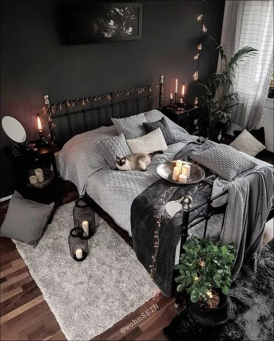 a mysterious artwork, some lights, candles in black candleholders and lanterns and moody textiles make the bedroom Halloween like