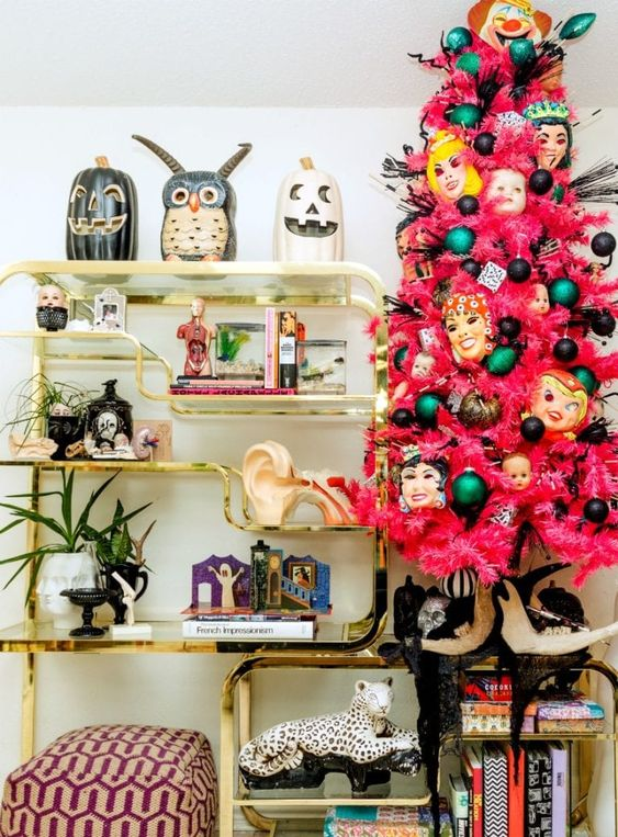 a pink Halloween tree with black and green ornaments, masks and feathers is a bold and spooky statement for a party