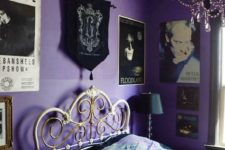 a purple and black bedroom with a bold gallery wall, a forged bed, a black crystal chandelier and a black lamp is gorgeous