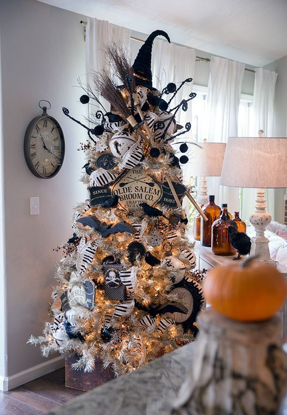 a silver Halloween tree decorated with a witch hat and brooms, with banners, garlands, bats and skulls