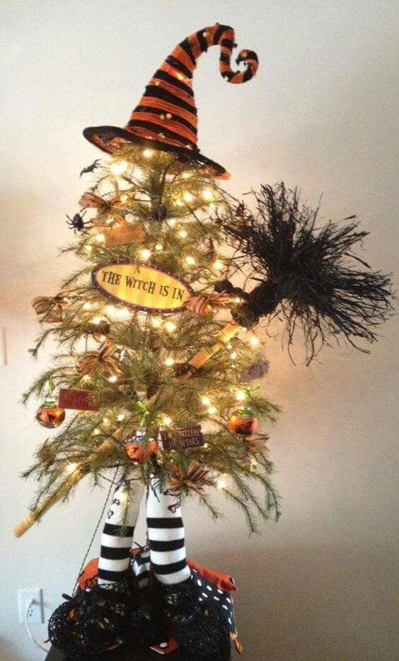 a small yet fun Halloween tree imitating a witch with legs, a hat and a broom decorated with ornaments and lights