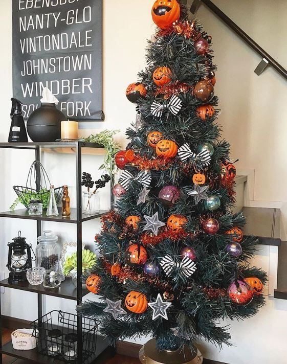 a stylish Halloween tree decorated with bows, colored ornaments, garlands and pumpkin ornaments