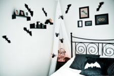 a stylish black and white Halloween bedroom spruced up with bats, spiders, a light cage and soem artworks on the wall