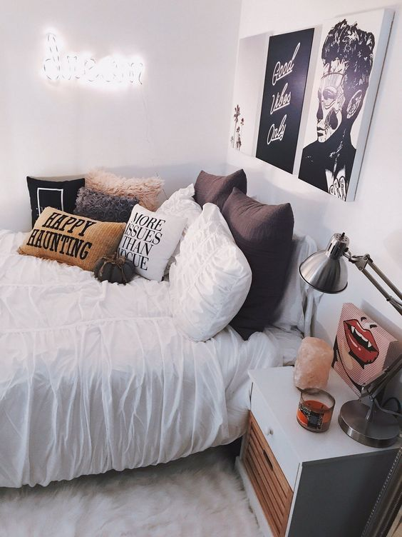 a stylish modern Halloween bedroom decorated with a bold gallery wall, an arrangement of pillows and a small fabric pumpkin