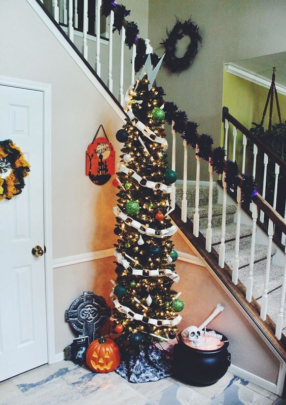 a tall Halloween tree in black decorated with banners, ornaments, lights and topped with a lightning