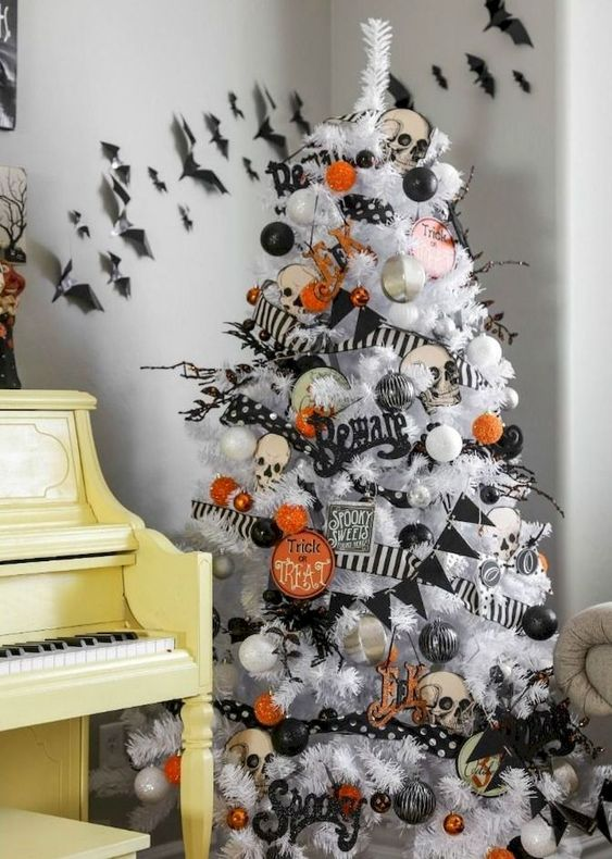 a white Halloween tree decorated with black and orange oranments, banners and garlands and skulls