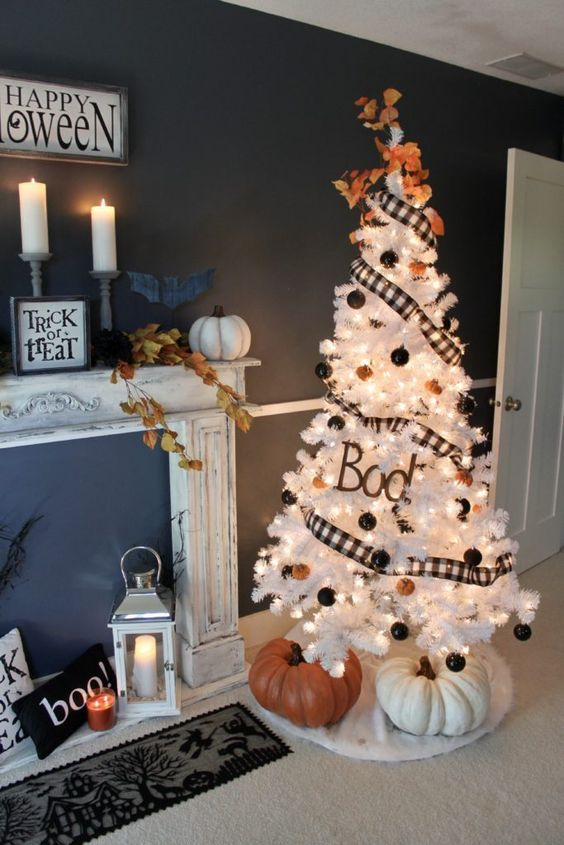 a white Halloween tree decorated with black and orange ornaments, a checked garland, lights and two large pumpkins under it