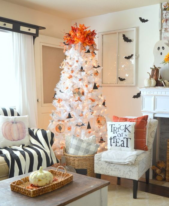 a white Halloween tree with lights, cardboard hats, fabric ornaments and a bold orange topper of leaves