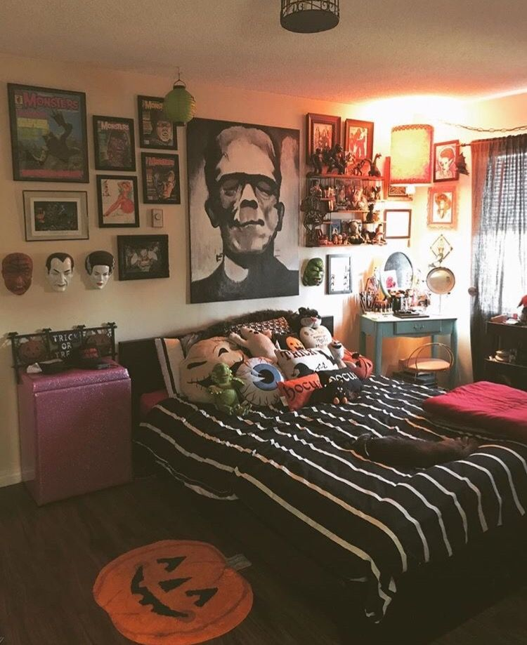 an arrangement of whimsy Halloween pillows, a scary gallery wall, a pumpkin rug and a striped bedspread