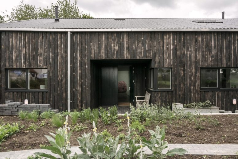 This home used to be a usual tractor shed, which was renovated and turned into a home, it was clad with scorched wood and resembles a barn