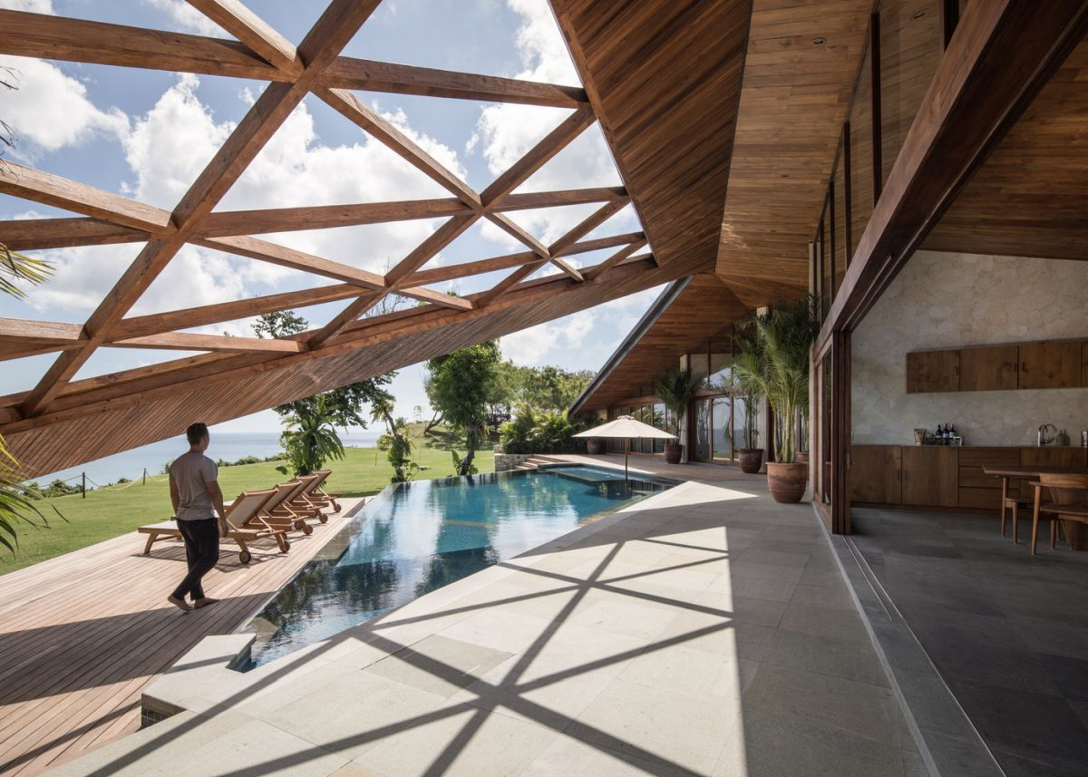 The indoor spaces are opened to outdoors with sliding doors and a sculptural geometric roof creates a seamless transition between them