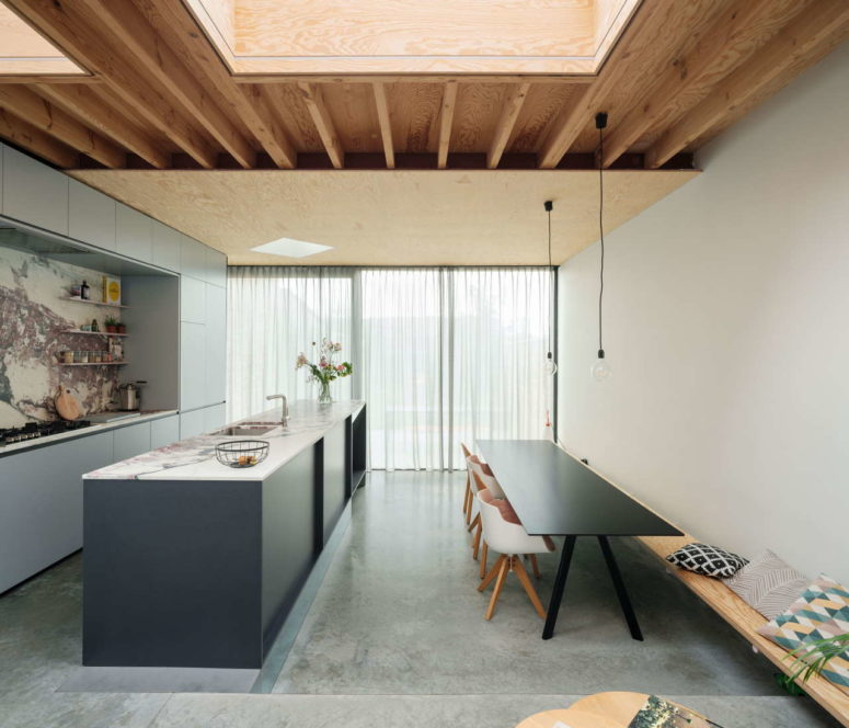 The kitchen features grey cabinets, a pink stone backsplash and a countertop plus a simple dining space with a table, a bench and chairs