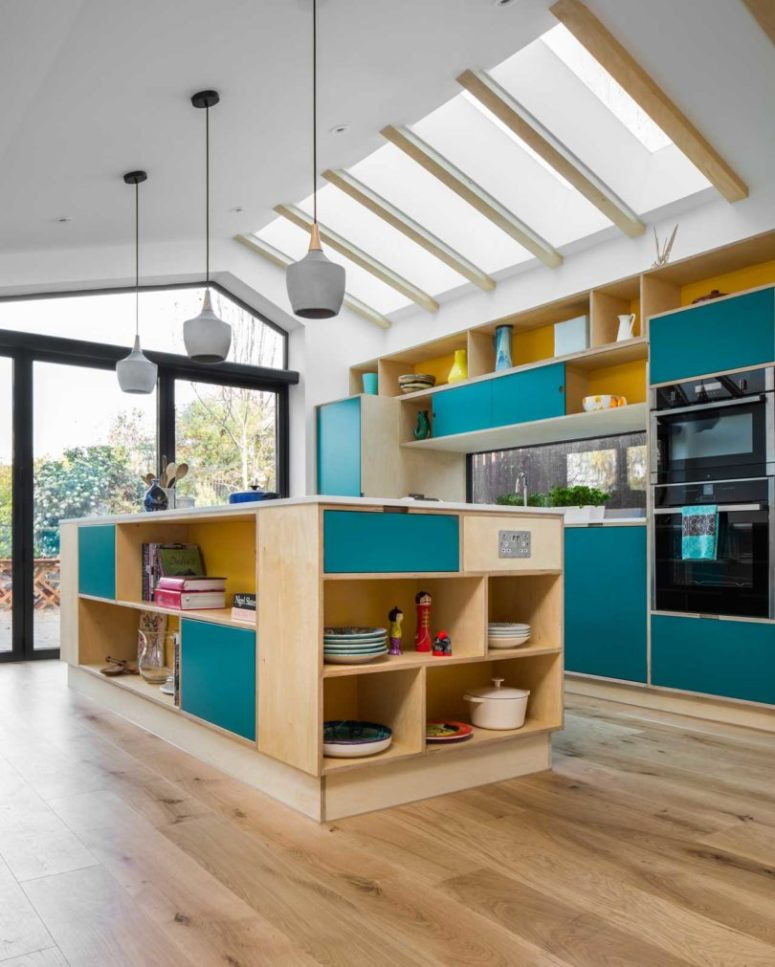 The kitchen is done in light-colored plywood and with teal panels, concrete pendant lamps and a window backsplash