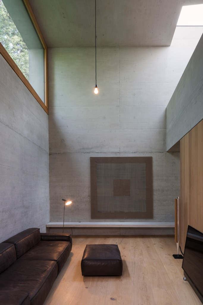 The living room is done with raw concrete, wood that softens the look and leather furniture