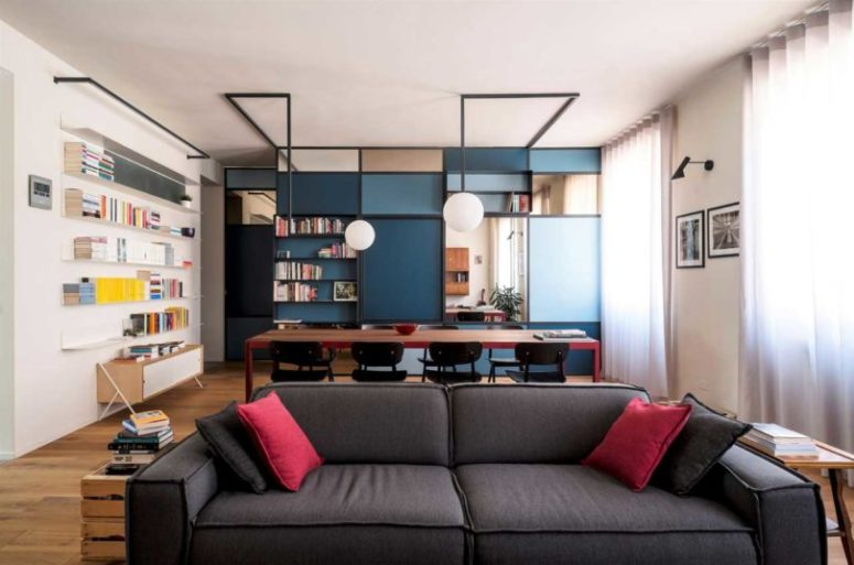 The main part of the dwelling is taken by a unique shelving unit in blue and navy, which divides the spaces and provides storage