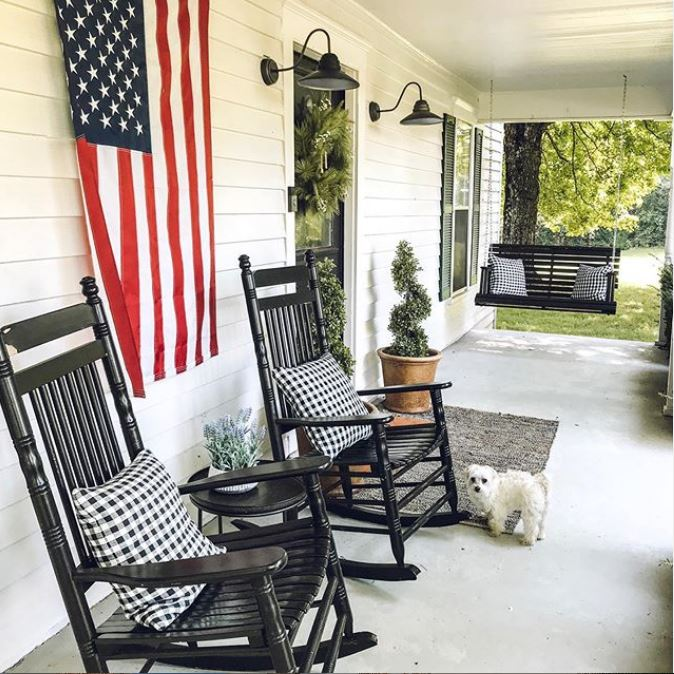 The porch is done with cozy black rockers, a hanging daybed, some potted greenery and lamps over the door