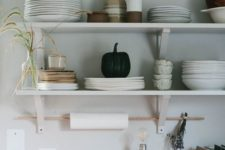 02 open minimalist shelves in the kitchen and a stick for hanging kitchen towels are a serene and cool kitchen
