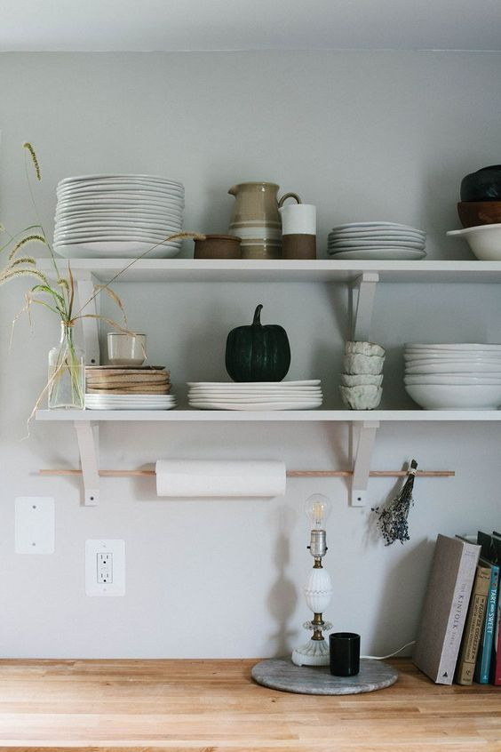 open minimalist shelves in the kitchen and a stick for hanging kitchen towels are a serene and cool kitchen