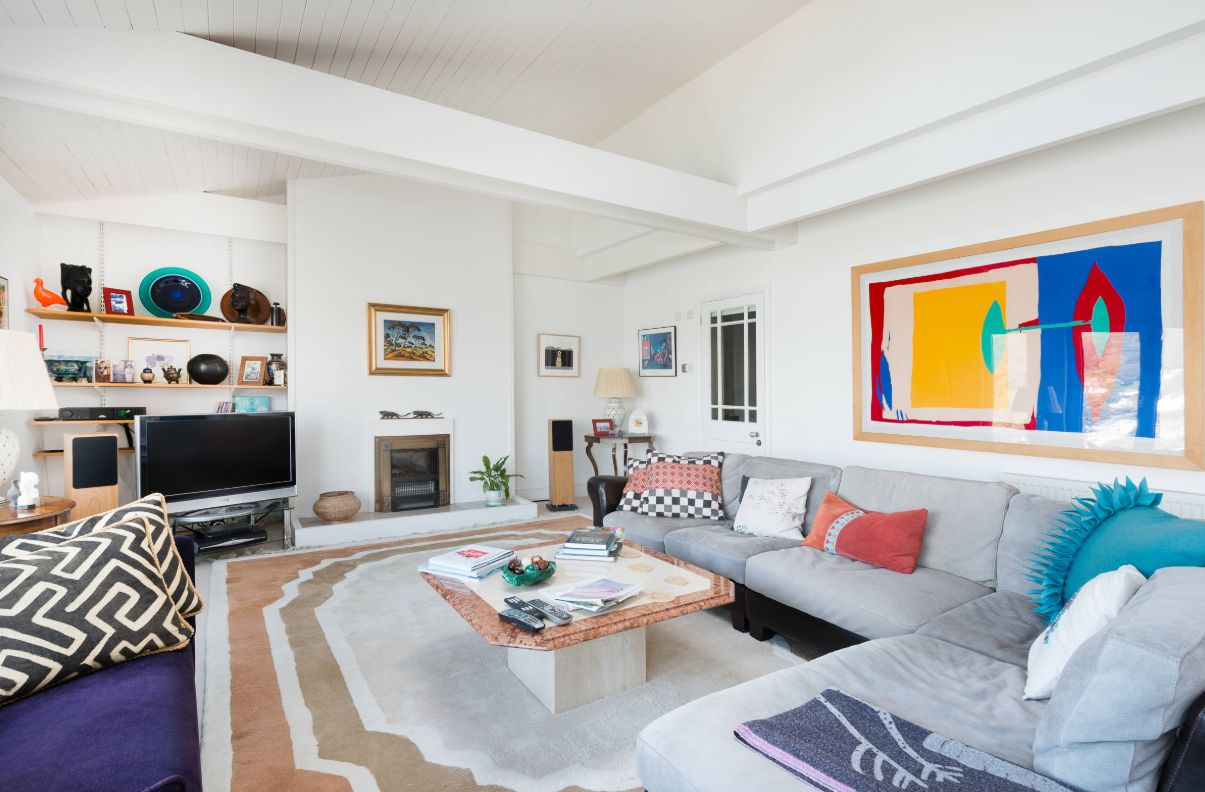 this basically neutral living room was spruced up with bright artworks, rugs, pillows for a bold and chic look
