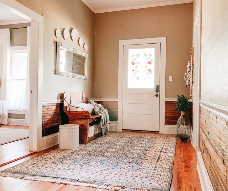 The entryway is cozy and simple, with a printed rug, some vintage plates and a vintage wooden bench