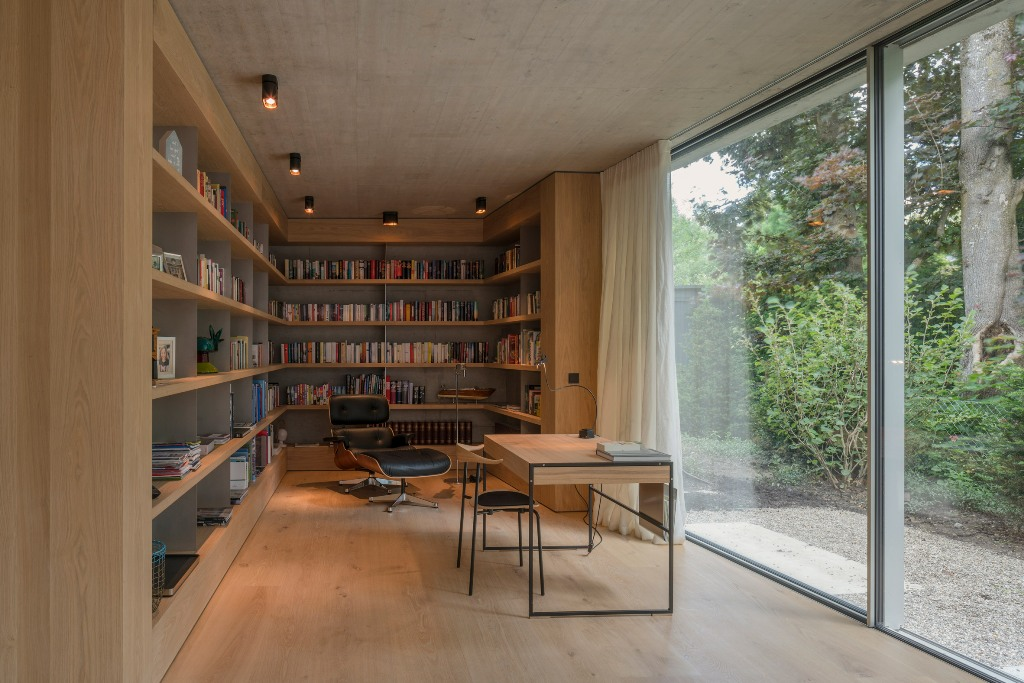 The home office is done wit a large bookshelf unit, a leather lounger and a desk with a chair