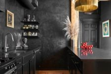 03 a creative vintage-inspired kitchen in black with a light-colored wooden ceiling and rich-colored woodne floor to warm up the space