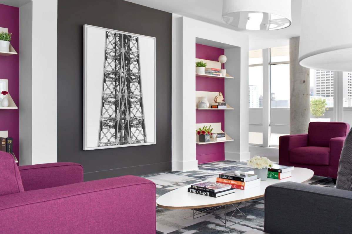 a monochromatic living room in grey and white was refreshed with fuchsia wall accents and furniture pieces