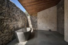a stone bathroom design with a wooden roof