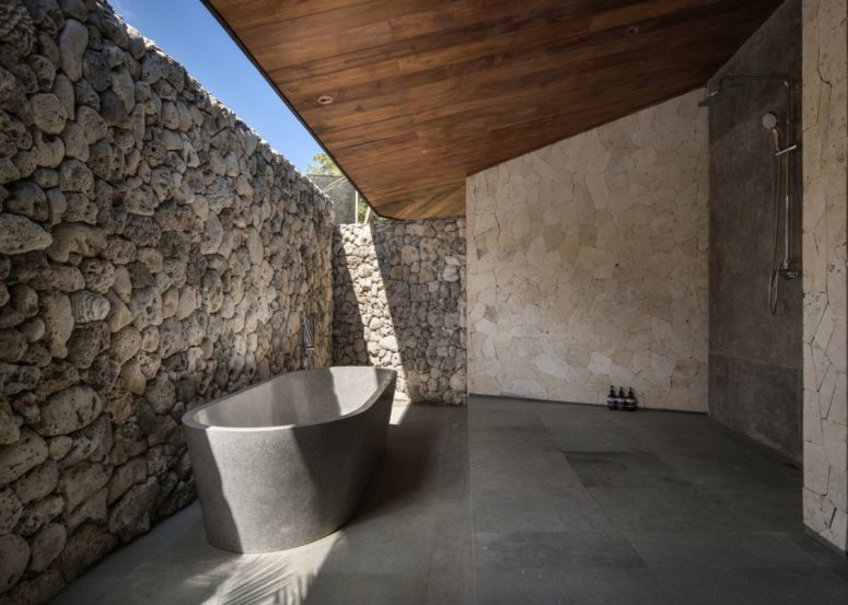 the bathroom with a shower and a tube of stone is indoor-outdoor with a stone wall that keeps privacy and a roof over it