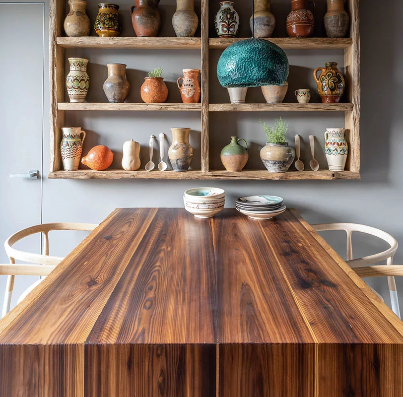 The dining space features a bold table, a creative teal pendant lamp and the rest of the collection of clay