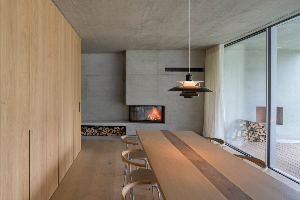The dining space was done with a fireplace, a firewood storage unit, contemporary furniture and there's an access to the terrace