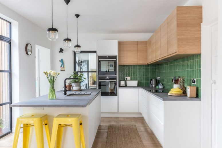 The kitchen is done with sleek cabinets and a green tile backsplash, a kitchen island with a concrete countertop and bright yellow stools
