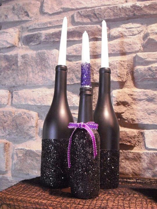 bottles painted matte black and blakc glitter with a purple bow and matching candles for Halloween candleholders