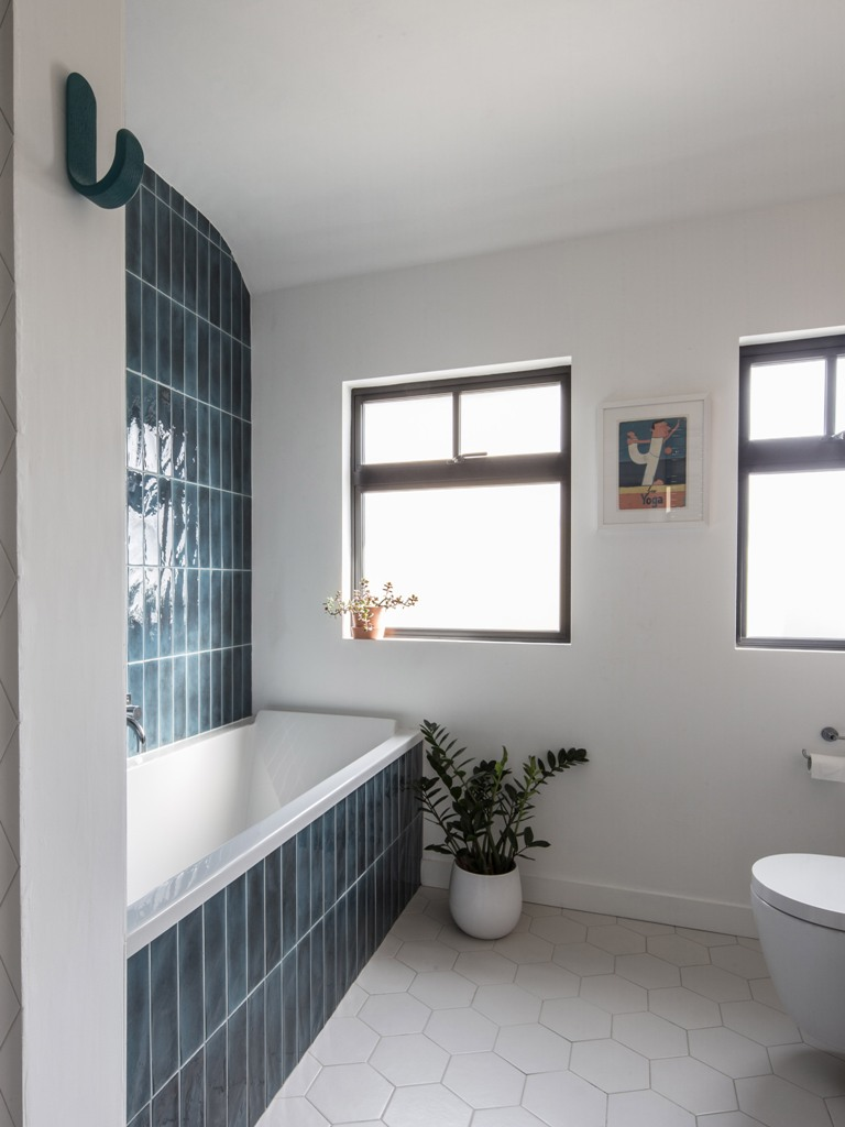 the bathroom is clad with teal tiles on the wall  and hexagon ones on the floor and features windows