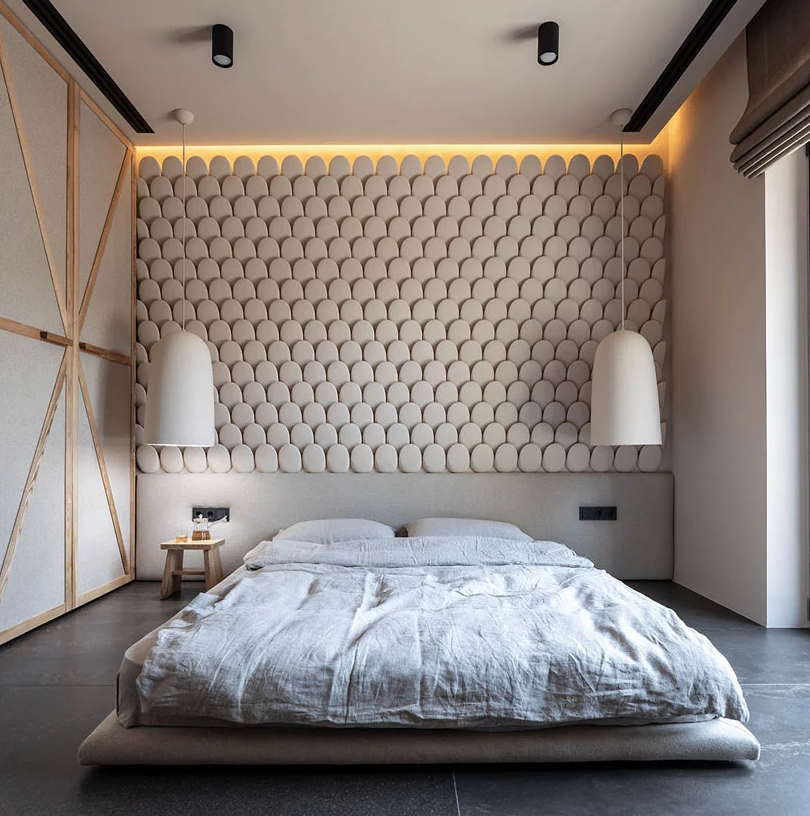 The bedroom is done with a scale statement wall, pendant lamps and a platform bed