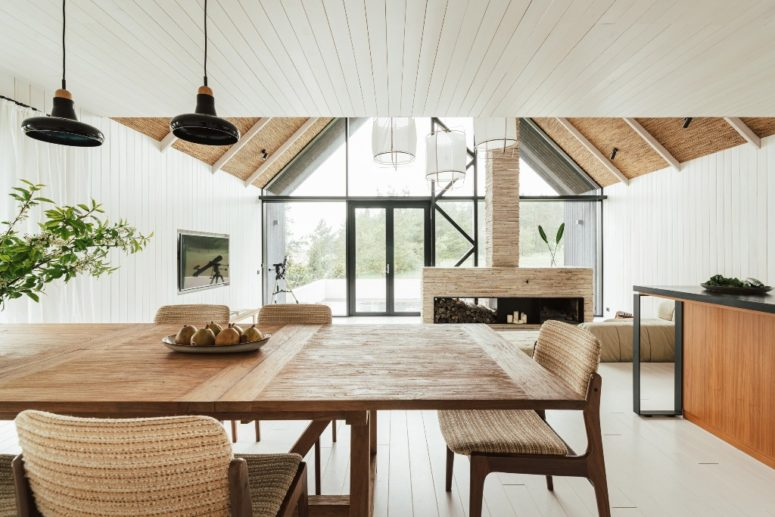 The interiors are all-neutral, with much wood and plywood, with a large fireplace, a cozy dining zone and lots of light coming through a glazed facade