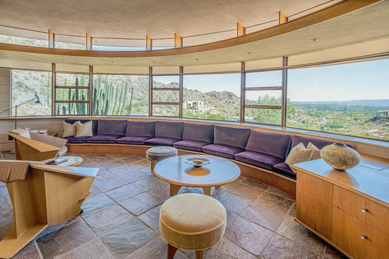 The living room features a circular bench, coffee tables and ottomans and sculptural chairs